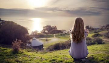 девушка сидит на холме