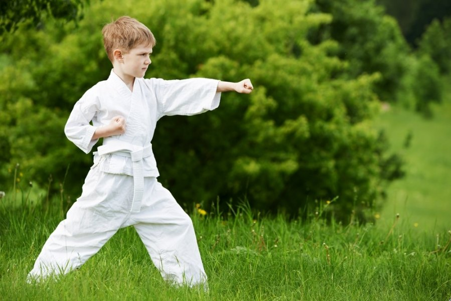 ребенок в кимоно на фоне зелени