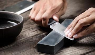 нож в руках на точильном камне